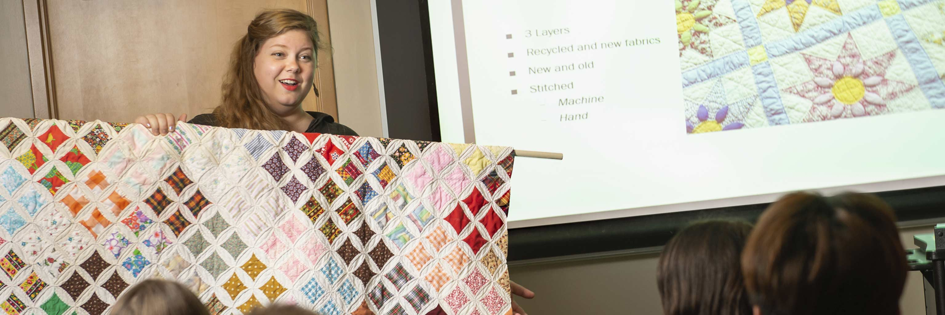A graduate student presents a quilt to the class.