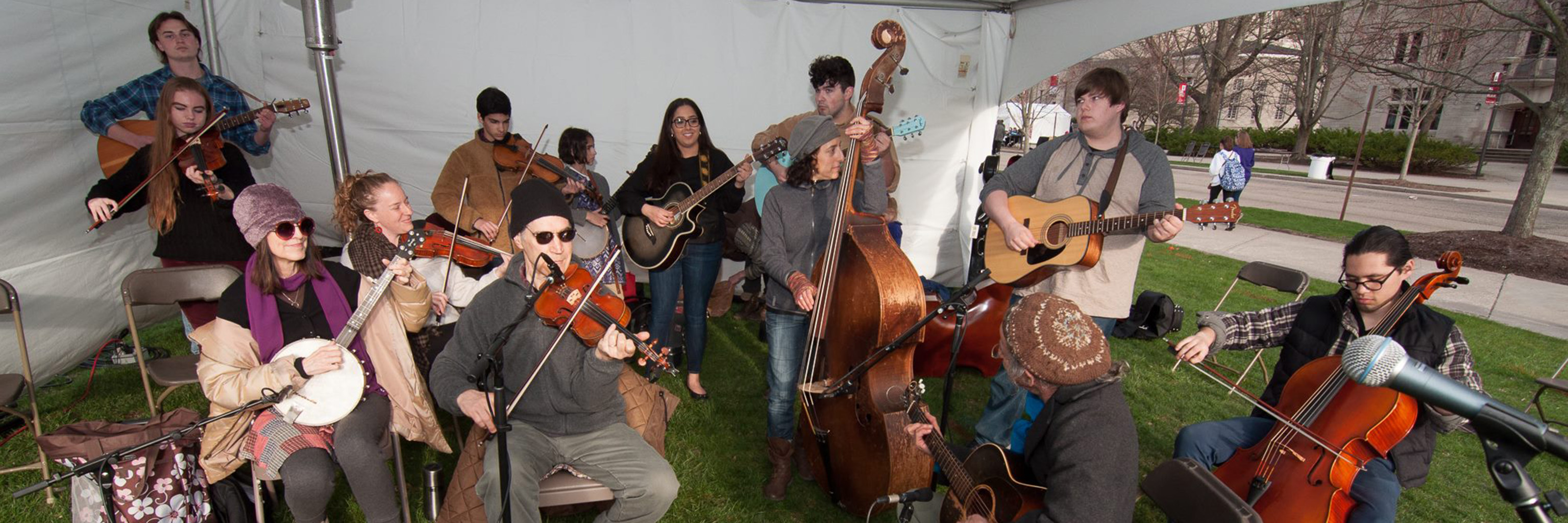 Musicians playing music in outdoor tent.