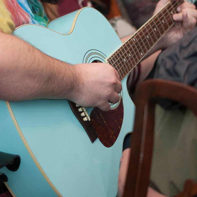 Close-up of person playing blue guitar.